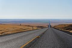 Landstraße durch das Rollen des goldenen Ackerlands Stockfoto