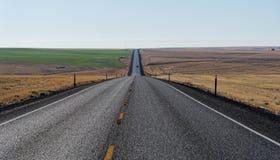 Landstraße durch das Rollen des goldenen Ackerlands Stockbild