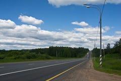 Landstraße durch grünen Waldsommertag Lizenzfreie Stockfotografie