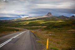 Landstraße durch Island-Gebirgslandschaft Stockfotos