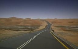Landstraße durch Wüstenhügel stockfotografie