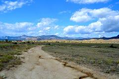 Landstraße an einem sonnigen Tag mit blauem Himmel und Wolken stockfotografie