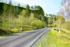 Landstraße entlang Hügel im Frühjahr Stockfotografie