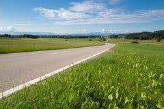 Landstraße im Bayern mit Ansicht zu den Alpen Stockfotos