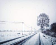 Landstraße im Bayern unter Schneefällen im Winter Lizenzfreies Stockbild