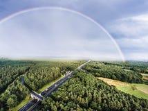 Landstraße im grünen Wald, bunter Regenbogen, Stadt netherlands lizenzfreie stockfotografie