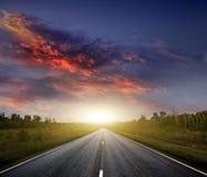 Landstraße mit einem dunklen Himmel stockbild