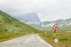 Landstraße mit einem Warnsignal mit einer Kuh Stockfotografie