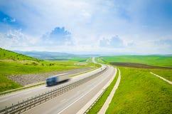 Landstraße mit Schnellfahrenlkw Stockfotos