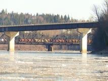 Landstraße und Eisenbahnbrücken über Frühlingsflusseis fließen Lizenzfreies Stockfoto