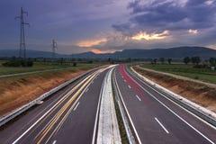 Landstraße zu den Himmeln mit drastischem Himmel und Auto schleppt die Führung der Weise stockbilder