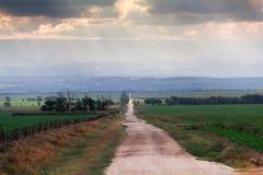 Landstraßeabflussrinne fängt das Gehen zum Horizont, zum Sonnenlicht und zu den Wolken auf stockbild