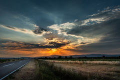 Landstraßen-Straße bei Sonnenuntergang Stockfotografie