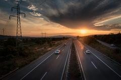 Landstraßen-Verkehr bei Sonnenuntergang Stockbild