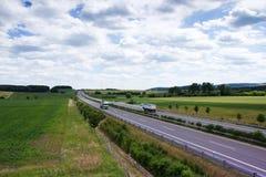 Landstraßentransport mit Autos und LKW Lizenzfreie Stockbilder