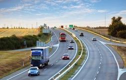 Landstraßenverkehr im Sonnenuntergang mit Autos und LKWs Lizenzfreie Stockfotos