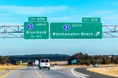 LandstraßenVerkehrsschild zu Hamptons New York an einem Tag des blauen Himmels lizenzfreie stockbilder