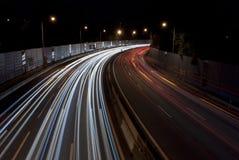 Landstraßenverkehr an der Nachtlangen Belichtung Stockfotos