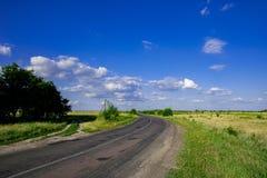 Landsväg i sommarfältlandskapet arkivfoto