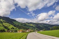 Landsväg i Westendorf, Brixental dal i Tirolean fjällängar, Österrike, Royaltyfri Bild