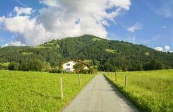 Landsväg i Westendorf, Brixental dal i Tirolean fjällängar, Österrike, Arkivfoto