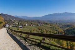 Landsväg som leder till en bergby Royaltyfria Bilder