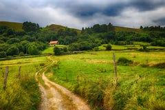 Landsväg till ett hus i bergen Arkivfoto