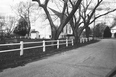 Landsväg, vitt trästångstaket, kyrklig byggnad royaltyfria foton