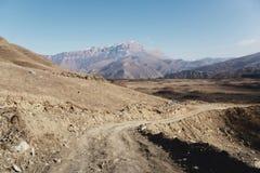 Landsvägen i bergen mot bakgrunden av epos vaggar royaltyfria foton