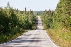 Landsväg i Lapland, Finland, på en solig sommardag Arkivfoton