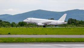 Landung des modernen Handelspassagierflugzeugs auf Flugplatz Rauch von unterhalb der Fahrgestelle hinter der Fläche stockbild
