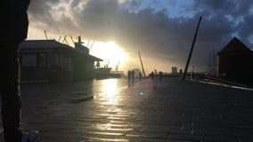 Landungsbruecken con las grúas del puerto silueteadas contra sistema dramático del cielo y del sol almacen de video