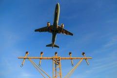 Landungsflugzeuge über Landescheinwerfern Lizenzfreie Stockfotos