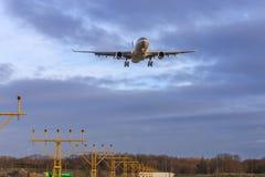 Landungsflugzeuge über Landescheinwerfern Stockfotografie