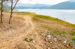 Landweg aan de meer en bergachtergrond stock fotografie