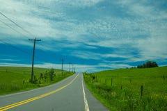 Landweg bergopwaarts met elektrische polen Royalty-vrije Stock Fotografie