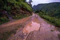 Landweg in de lentebergen met veel modderige vulklei na de regen - Sainj-Vallei, Kullu, Himachal, India royalty-vrije stock afbeeldingen
