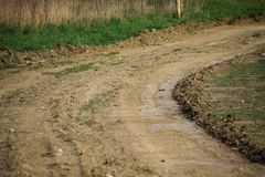 Landweg die door een nivelleermachine wordt genivelleerd Weg in dorp stock afbeelding