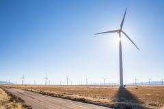 Landweg door windlandbouwbedrijf met zonnestraal stock foto
