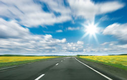 Landweg en blauwe bewolkte hemel Royalty-vrije Stock Foto's