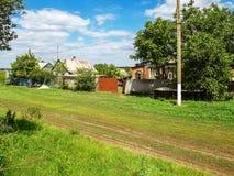 Landweg in het dorp, de de lentedag en het groene gras rond Royalty-vrije Stock Afbeeldingen