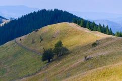 Landweg hoog in de bergen die naar het dorp in de vallei daalt stock foto's