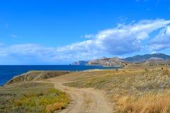 Landweg langs het overzees op een zonnige dag met blauwe hemel en wolken royalty-vrije stock afbeeldingen