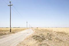 Landweg met elektriciteitspylonen op een de zomerdag Royalty-vrije Stock Afbeelding