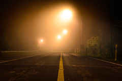 Landweg met nachtlicht onder de mist royalty-vrije stock afbeeldingen
