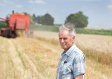 Landwirt auf Feld mit Mähdrescher harbester lizenzfreie stockbilder