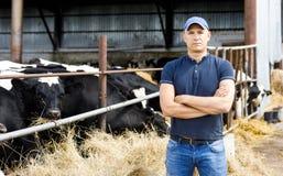 Landwirt am Bauernhof mit Milchkühen lizenzfreie stockbilder