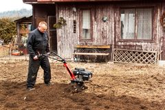 Landwirt, der auf dem Gebiet arbeitet Frühlingsarbeit über den Bauernhof Mann, der den Garten pflügt Stockfotos