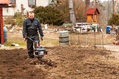 Landwirt, der auf dem Gebiet arbeitet Frühlingsarbeit über den Bauernhof Mann, der den Garten pflügt Stockfoto