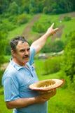 Landwirt, der auf sein pflügendes Land auf Hügel zeigt Stockbilder